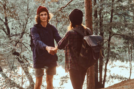 Romantic happy hikers are watching sunset in green lush forest. They have hats and backpacks.