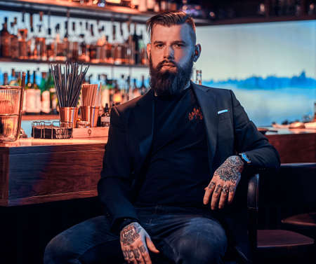Attractive brutal man is sitting near bar counter. He has tattoes and beard.