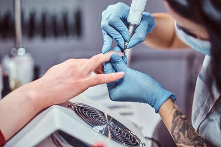 Hardware manicure in a beauty salon. Manicure procedure in progress - Beautician master using nail drill to trim and remove cuticles Stock Photo