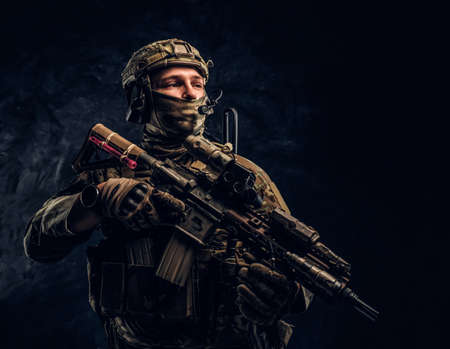 Fully equipped soldier in camouflage uniform holding an assault rifle. Studio photo against a dark textured wall