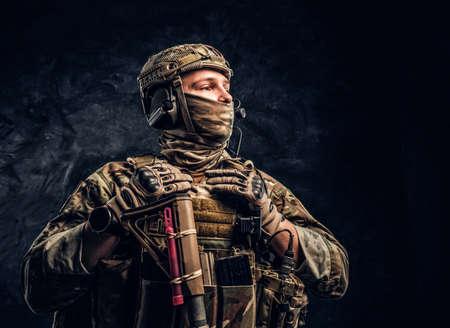 Modern special forces soldier in camouflage uniform looking sideways. Studio photo against a dark textured wall. Reklamní fotografie