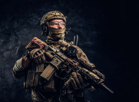 Fully equipped special forces soldier in camouflage uniform holding an assault rifle. Studio photo against a dark wall Reklamní fotografie