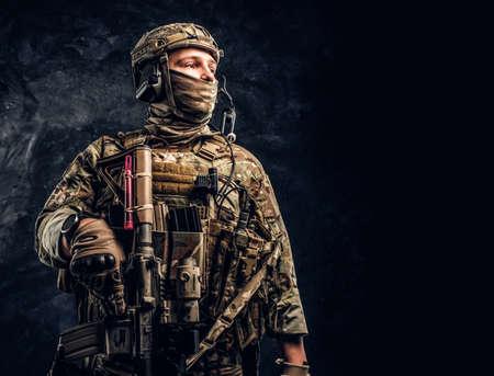 Moderner Soldat der Spezialeinheiten in Tarnuniform, der seitlich schaut. Studiofoto gegen eine dunkle strukturierte Wand.