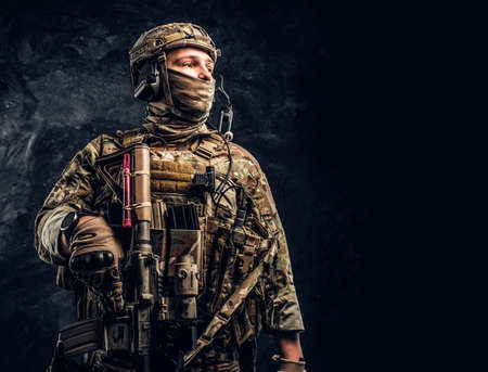Nowoczesny żołnierz sił specjalnych w mundurze kamuflażowym patrzącym z boku. Studio fotografii na tle ciemnej ściany z teksturą.