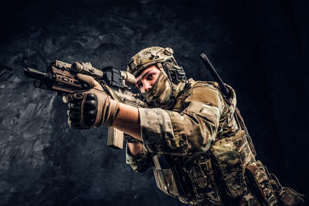 Private security service contractors, the elite special unit, full protective soldier holding assault rifle aiming at the target. Studio photo against a dark wall.