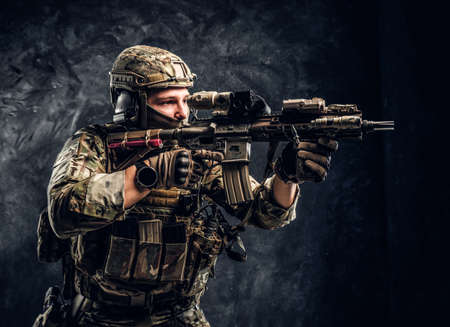 Close-up studio photo against a dark textured wall. The elite unit, special forces soldier in camouflage uniform holding an assault rifle with a laser sight and aims at the target Reklamní fotografie