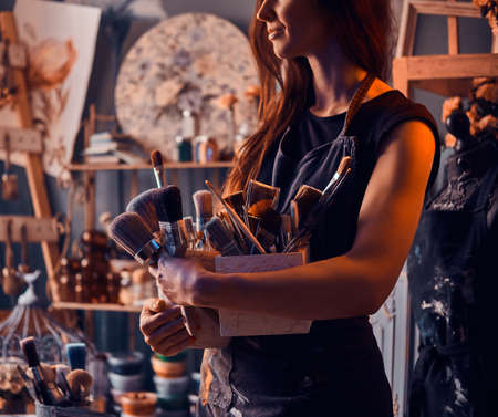 Young talented painter is posing with brushes in her own art studio.