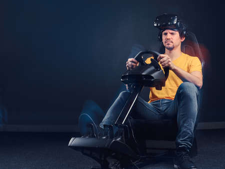 Man dressed in yellow shirt and jeans wearing VR headset driving on car racing simulator cockpit with seat and wheel.