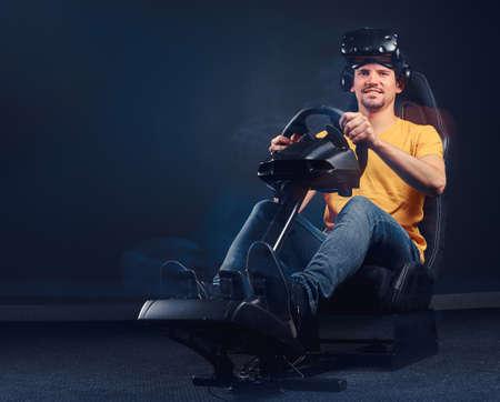 Hombre alegre vestido con camisa amarilla y jeans con casco de realidad virtual sentado en un simulador de carreras de coches, mirando a la cámara.