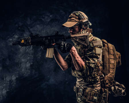 Special forces soldier in protective uniform holding an assault rifle and aim at the enemy. Studio photo against a dark textured wall