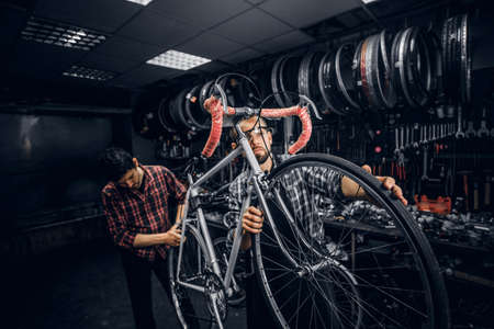 Two attractive mans are working on bicycle fixing at busy workshop.