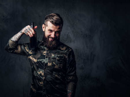 Stylish bearded hipster guy in military shirt holding a craft beer and looking at a camera. Studio photo against a dark wall