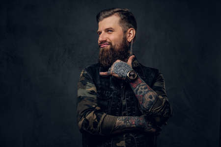 Portrait of a funny bearded guy with tattooed hands showing Shaka sign and looking at a camera. Studio photo against a dark wall 免版税图像