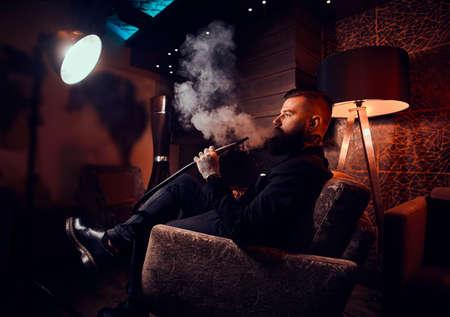 Brutaler tätowierter Mann macht schönen nebligen Dampf, während er sich in der Nähe des Kamins entspannt und Wasserpfeife raucht. Standard-Bild
