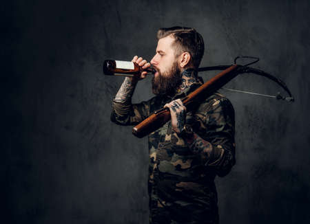 A bearded tattooed hipster guy in military shirt holding a medieval crossbow and drinks a craft beer. Studio photo against a dark wall
