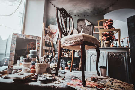 Photo of artists pretty soiled workshop with chair ready for restouration on the table.