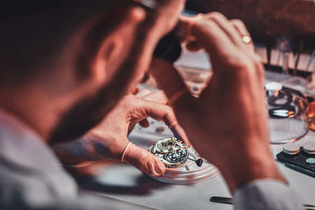 Mature clock master is fixing old watch for a customer at his busy repairing workshop.