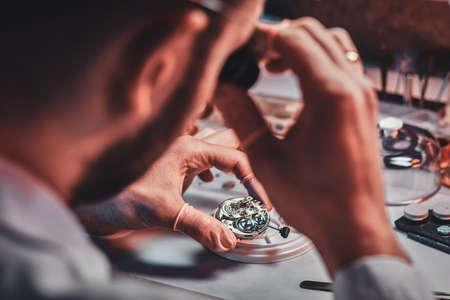 Un maître d'horloge mature répare une vieille montre pour un client dans son atelier de réparation occupé.