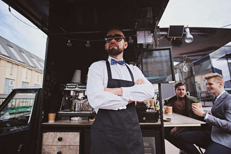 Groomed elegant barista in sunglasses is standing crossed his hands next to his small coffeeshop. Stock Photo