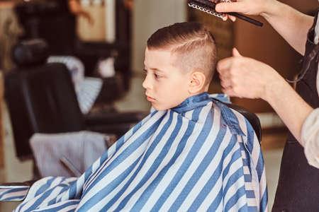 Un drôle de petit garçon se prépare pour l'école dans un salon de coiffure branché avec un coiffeur mature.