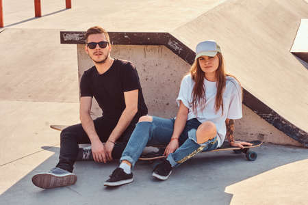 Attractive young couple is sitting at sunny skatepark with their longboards next to the ramp.