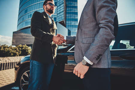 Low angle photo of two smart elegant men, which have a deal about car. They are doing handshake.