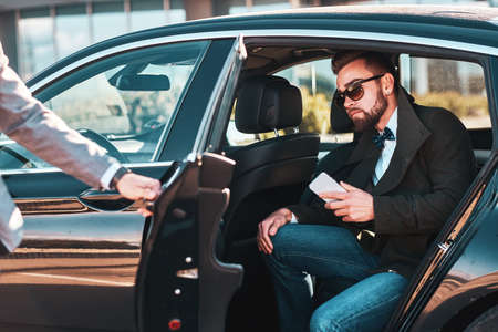 Busy nice businessman in sunglasses is sitting in the car while his elegant assistant is opening door for him.