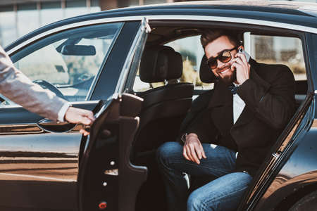 Busy smiling businessman in sunglasses is talking by smartphone while his elegant assistant is opening door for him. Stok Fotoğraf