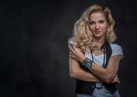 Charming curly blonde girl dressed in a white t-shirt and waistcoat wears a lot of accessories and wristwatch, posing with crossed arms at a studio. Isolated on a dark textured background. Imagens - 124774868