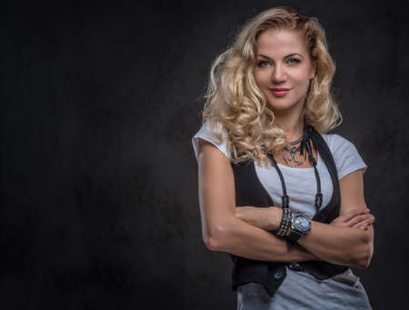 Sensual curly blonde female dressed in a white t-shirt and waistcoat wears a lot of accessories and wristwatch, posing with crossed arms at a studio. Isolated on a dark textured background. Imagens