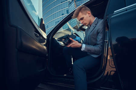 Young attractive buisnisman is looking to his mobile phone while sitting in the car. Stockfoto