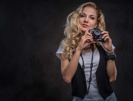 Sensual curly blonde girl photographer dressed in a white t-shirt and waistcoat wears a lot of accessories and wristwatch, posing with a camera at a studio. Isolated on dark textured background. Imagens - 124774873