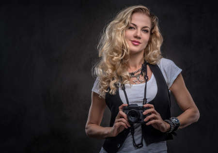 Sensual curly blonde girl photographer dressed in a white t-shirt and waistcoat wears a lot of accessories and wristwatch, posing with a camera at a studio. Isolated on dark textured background. Imagens - 124774874