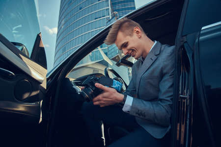 Young attractive buisnisman is looking to his mobile phone while sitting in the car. Stock Photo