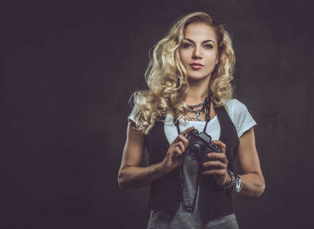 Beautiful curly blonde female photographer dressed in a white t-shirt and waistcoat wears a lot of accessories and wristwatch, posing with a camera at a studio. Isolated on dark textured background. Stock Photo - 124774876