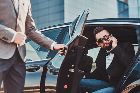 Busy nice businessman in sunglasses is talking by smartphone while his elegant assistant is opening door for him.