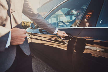 Smart attractive businessman is sitting in the car car while his young assistant is opening door for him.