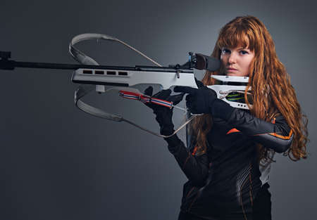 Redhead female Biathlon champion aiming with a competitive gun in a studio over grey background.Redhead female Biathlon champion aiming with a competitive gun in a studio over grey background.