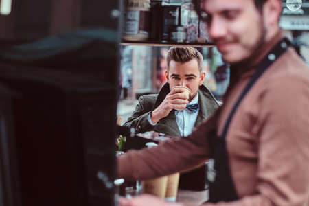 Handsome groomed man is enjoying his coffee while sitting at coffeeteria. There are working barista at frontground. Stock Photo