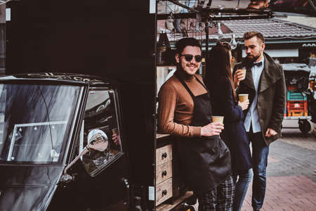 Attractive happy barista in sunglasses took a coffeebreak at his own coffeeshop.