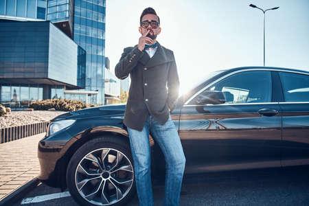 Gut aussehender Mann im Mantel steht in der Nähe seines neuen Autos, während er auf dem Parkplatz raucht.