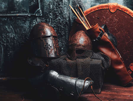 Still life with ancient shield, two rusted helmets, quiver of arrows and chain mail.