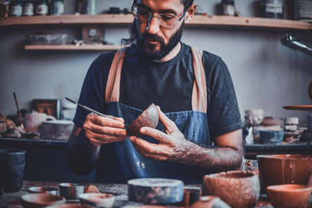 Diligent entusiastic master in glasses at his  pottery studio is workig for a new dish.