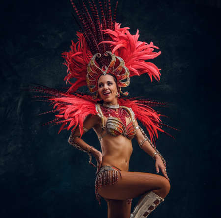 Young attractive brasil dancer in red feather costume is dancing at small dark studio.