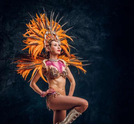 Hermosa mujer joven en traje de plumas especial está bailando en el estudio. Foto de archivo