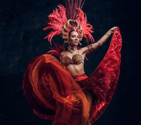 Une danseuse talentueuse et joyeuse en costume de plumes rouges pose dans un petit studio sombre.