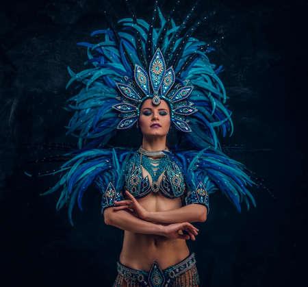 Schöne Tänzerin steht kreuzt ihre Hände. Sie trägt ein blaues Federkostüm. Standard-Bild