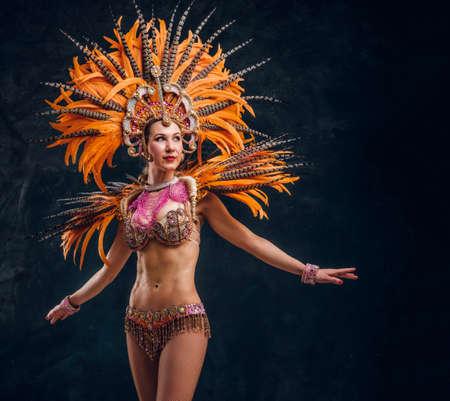 Schöne junge Frau in speziellem Federkostüm tanzt im Studio. Standard-Bild