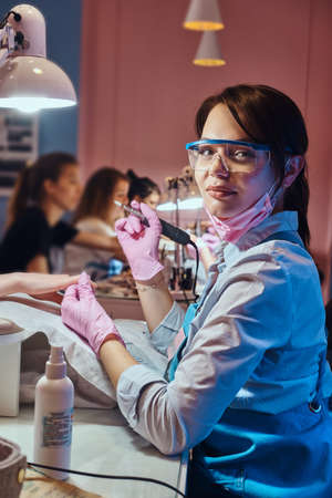 Attractive cheerful manicurist is posing for photographer while doing maicure for customer.