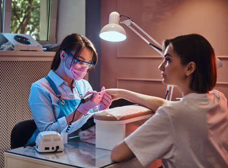 Young cheerful manicure master at her own workplace with client is working on womans nails. Stock Photo